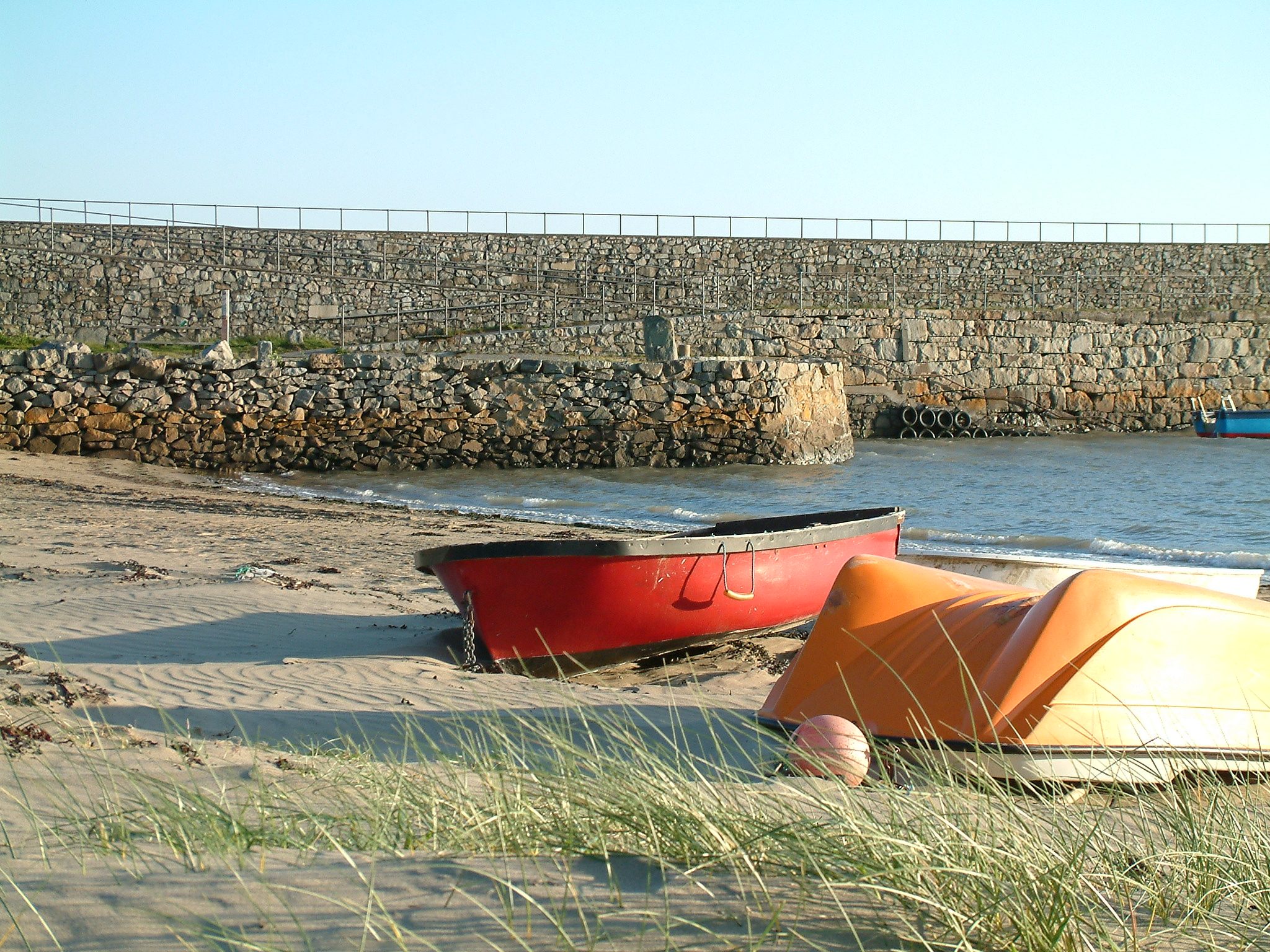 A view of the beach at Trefor with boats and jetty Llŷn Peninsula