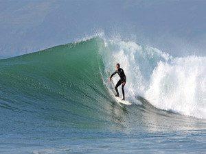 A surfer surfing big wave at Porth Neigwl Hells Mouth beach Llyn Peninsula North Wales