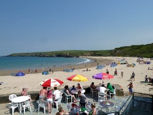 People eating and drinking outside the cafe at Porthor Porth Oer Whistling Sands Llyn Peninsula