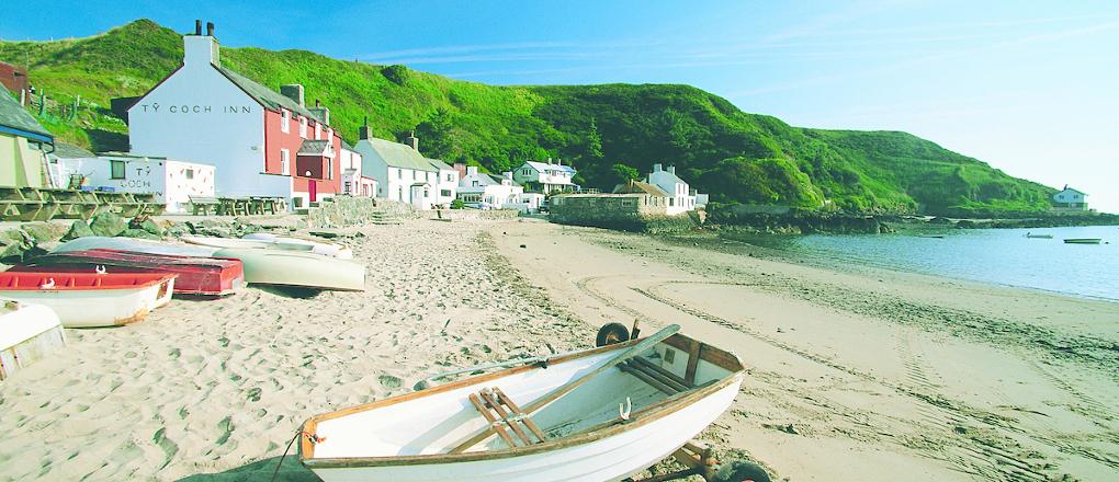 A view of boats and Ty Coch Inn at Porthdinllaen beach Morfa Nefyn Llyn Peninsula
