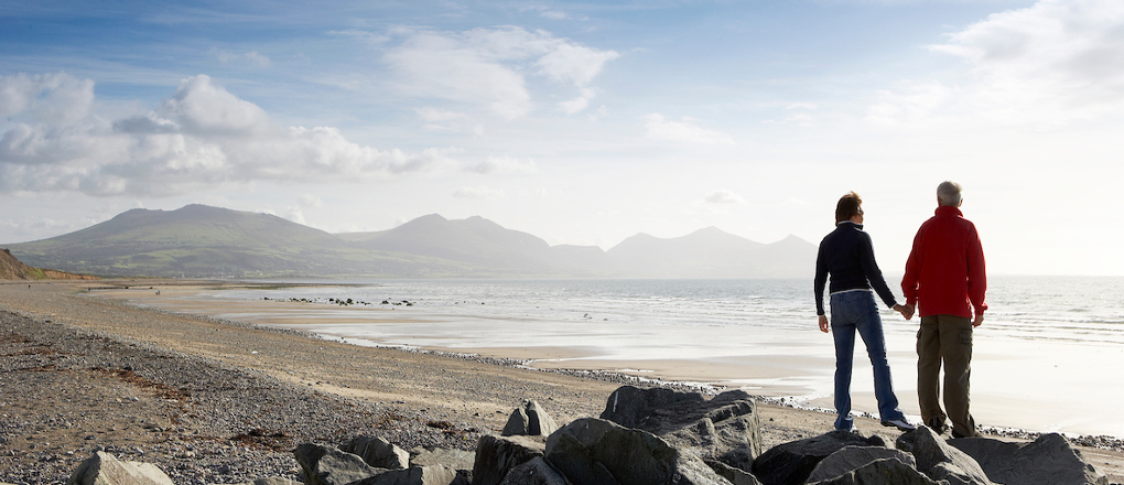 Couple overlooking the beach at Dinas Dinlle Caernarfon Llyn Peninsula North Wales
