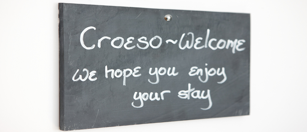 A slate sign with chalk writing saying croeso welcome