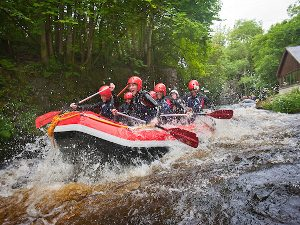 Paddling in an inflatable down rapids at the National White Water Rafting Centre Bala