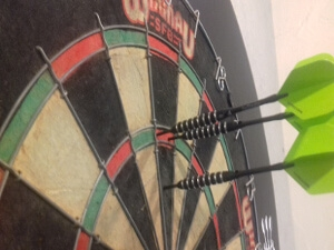 Dart board with three green darts Gors-lŵyd Games Room