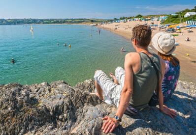 Couple sitting on rocks overlooking Abersoch beach and Abersoch bay