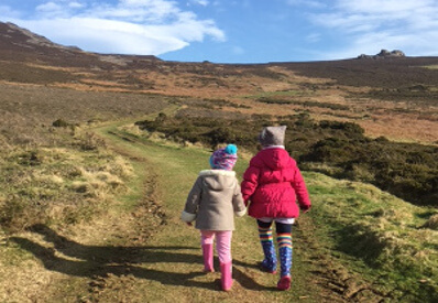 young girls walking up a mountain hand in hand